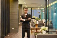 Asiatischer Mann des Geschäfts, der vor Luxuswohnzimmer in Umb. lächelt lizenzfreies stockbild