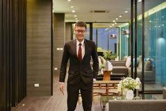 Asiatischer Mann des Geschäfts, der vor Luxuswohnzimmer in Umb. lächelt lizenzfreie stockbilder