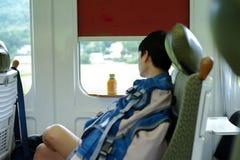 Asiatischer Mann des Porträts, der während des Reisens mit dem Zug Nickerchen macht lizenzfreie stockfotografie