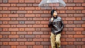Asiatischer Mann in einer Brown-Jacke mit einem klaren Regenschirm Lizenzfreies Stockfoto