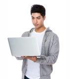 Asiatischer Mann gelesen auf der Laptop-Computer lizenzfreie stockbilder