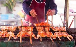 Asiatischer Mann grillt Hühner auf dem Grill Lizenzfreies Stockfoto