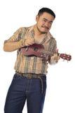 Asiatischer Mann im Plaid, das Ukulele spielt Stockfotografie