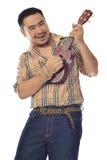 Asiatischer Mann im Plaid, das Ukulele spielt Lizenzfreie Stockfotos