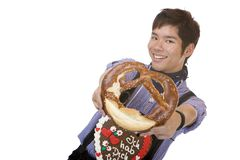 Asiatischer Mann in Lederhose hält Oktoberfest Brezel an Stockbilder