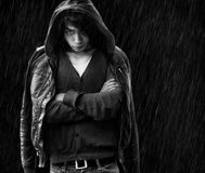 Asiatischer Mann mit den Querhänden unter Regen Stockbild