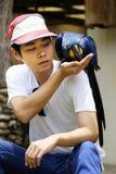 Asiatischer Mann mit schönem Hyazinthenkeilschwanzsittichpapageien Stockfoto