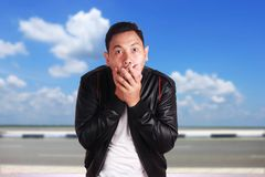 Asiatischer Mann nah entsetzt seinem Mund mit den Händen Stockfotografie