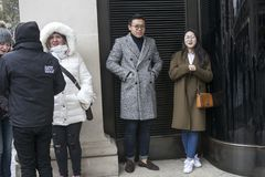 Asiatischer Mann und Frau stehen die schwarze Tür unter dem Bogen bereit, der auf den Regen auf Covent-Garten wartet Stockfotografie