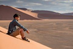Asiatischer Mannphotograph, der auf Sanddüne sitzt Lizenzfreies Stockbild