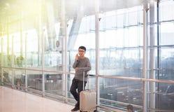Asiatischer Mannreisender, der Handy im Flughafen, Lebensstil unter Verwendung des Handyverbindungskonzeptes, fühlend und des Läc Lizenzfreie Stockfotos
