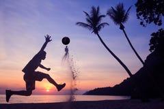 Asiatischer Mannspielfußball auf dem Strand am frühen Morgen des Sonnenaufgangs stockbilder
