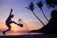 Asiatischer Mannspielfußball auf dem Strand am frühen Morgen des Sonnenaufgangs lizenzfreies stockbild