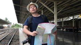 Asiatischer Manntaschen-Satztourist mit Karte im Bahnhof bei Thailand