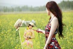 Asiatischer Mädchenanstrich auf dem Rapsgebiet Stockbild