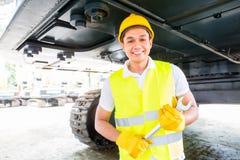 Asiatischer Mechaniker, der Baumaschine repariert Lizenzfreie Stockbilder