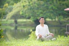 Asiatischer meditierender Mann Stockfotos