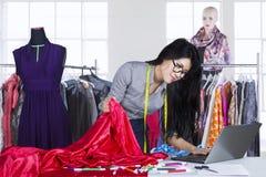 Asiatischer Modedesigner, der an Laptop arbeitet Lizenzfreies Stockfoto