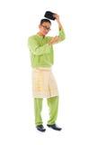 Asiatischer moslemischer Mann mit traditionellem malaysischem Kostüm in lächelndem acti Lizenzfreie Stockfotografie