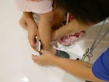 Asiatischer Mutter und die Hände des Verkäufers, die auf einem Schuh und ihre wenige Tochter haben versucht ihn auf eine Entschei stockfotografie