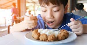 Asiatischer netter Junge essen Frühstück und Schauenkamera mit Lächelngesicht stockfoto