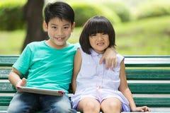 Asiatischer netter Junge und kleines Mädchen sind Lächeln und Schauen der Kamera Lizenzfreies Stockbild
