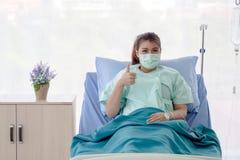 Asiatischer Patient, der auf Krankenhausbett mit den Handzeichendaumen-oben sitzt stockfotos