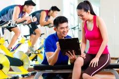 Asiatischer persönlicher Trainer mit Frau in der Eignungsturnhalle Stockfotografie