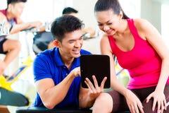 Asiatischer persönlicher Trainer mit Frau in der Eignungsturnhalle lizenzfreies stockbild