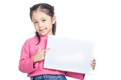 Asiatischer Punkt des kleinen Mädchens zu einem leeren Zeichen und zu einem Lächeln stockfoto
