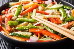 Asiatischer Salat von Karotten, von Erbsen, von Pfeffern, von Gurken und von Zwiebelnahaufnahme auf einer Platte horizontal stockfoto