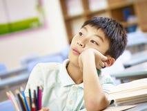 Asiatischer Schüler, der im Klassenzimmer träumt stockbilder