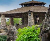 Asiatischer Steingazebo mit Grasdach und hängenden Laternen Stockbild