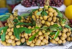 Asiatischer Straßenlandwirtmarkt, der frischen Longan verkauft Stockfotos