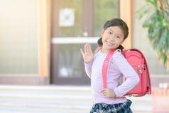Asiatischer Student, der zur Schule und zum Zum Abschied winken geht Lizenzfreies Stockfoto