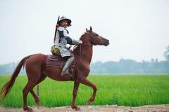 Asiatischer thailändischer Krieger im traditionellen Rüstungsklagen-Reitpferd im ländlichen Bauernhofhintergrund Kriegs-Kostümkon stockfotos