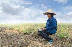Asiatischer thailändischer Landwirt, der Laptop-Computer auf dem Reisgebiet verwendet Lizenzfreie Stockfotos