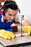Asiatischer Tischler oder Arbeitskraft sahen an mit Holz Stockfoto