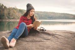 Asiatischer Tourist des entspannenden Momentes, der ein Buch auf Felsen liest stockbilder