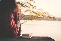 Asiatischer Tourist des entspannenden Momentes, der ein Buch auf Park liest lizenzfreie stockbilder