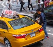 Asiatischer Tourist nimmt das gelbe Fahrerhaus in Manhattan, NYC Stockfoto