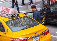Asiatischer Tourist nimmt das gelbe Fahrerhaus in Manhattan, NYC Lizenzfreies Stockbild