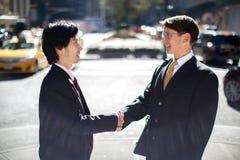 Asiatischer und kaukasischer Geschäftsmann, der Hände rüttelt Lizenzfreie Stockfotos