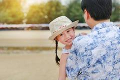 Asiatischer Vater trägt seine Tochter, die auf dem Strand lächelt stockfotografie