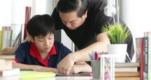 Asiatischer Vater und Sohn, die auf dem Tisch Hausarbeit im Wohnzimmer tut stock video