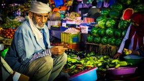 Asiatischer Verkäufer saß durch den Marktstall, der Lebensmittel verkauft stockfotografie