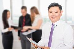 Asiatischer vollziehendchef, der Tabletten-PC mit seinem Geschäftsteam verwendet Lizenzfreie Stockfotos