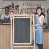 Asiatischer weiblicher Caféinhaber mit leerem Brett Lizenzfreies Stockfoto