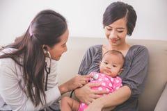 Asiatischer weiblicher Kinderarzt, der ein Baby im Mutterla überprüft Lizenzfreie Stockfotografie