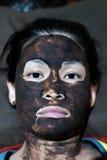 Asiatischer weiblicher Kopf umfasst mit Schlammgesichtsbehandlungsmaske Stockfotografie